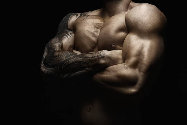 strong athletic man showes naked muscular body - mann schulter tattoos stock-fotos und bilder