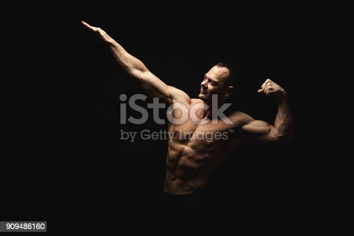 909486418 istock photo Strong athletic man showes naked muscular body 909486160