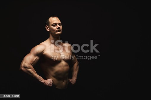909486418 istock photo Strong athletic man showes naked muscular body 909914788