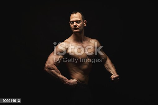 909486418 istock photo Strong athletic man showes naked muscular body 909914910