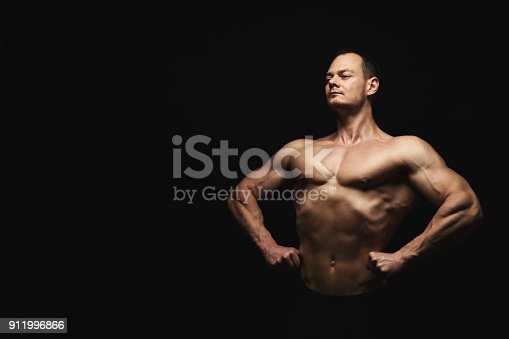 909486418 istock photo Strong athletic man showes naked muscular body 911996866
