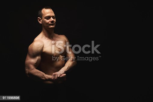 909486418 istock photo Strong athletic man showes naked muscular body 911996898