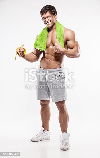 istock Strong Athletic Man  showing muscular body and eating a banana 679357004