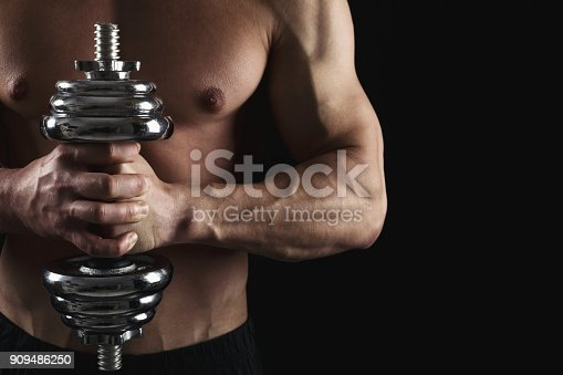 909486418 istock photo Strong athletic man with dumbbell showes naked muscular body 909486250