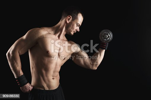 909486418 istock photo Strong athletic man with dumbbell showes naked muscular body 909486330