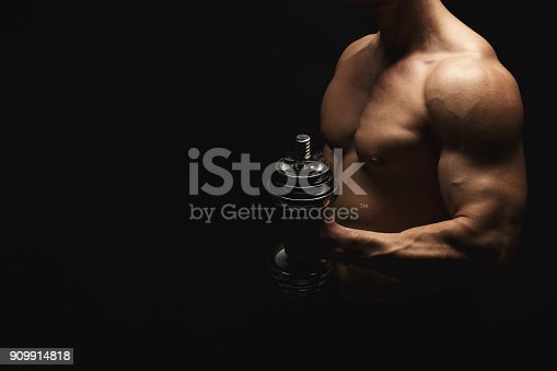 909486418 istock photo Strong athletic man with dumbbell showes naked muscular body 909914818