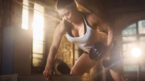 mujer atlética fuerte hace ejercicio de press de banca con mancuernas como parte de su cruzada fitness culturismo gimnasio ejercicio. - mancuerna fotografías e imágenes de stock