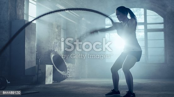 istock Strong Athletic Woman Exercises with Battle Ropes as Part of Her Cross Fitness Gym Workout Routine. She's Covered in Sweat and Training Takes Place in a Abandoned Factory Remodeled into Gym. 844489120