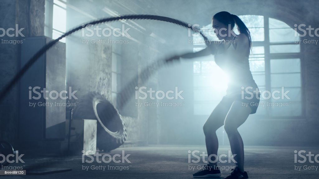 Strong Athletic Woman Exercises with Battle Ropes as Part of Her Cross Fitness Gym Workout Routine. She's Covered in Sweat and Training Takes Place in a Abandoned Factory Remodeled into Gym. stock photo