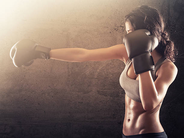 Strong athletic woman with gloves punching stock photo