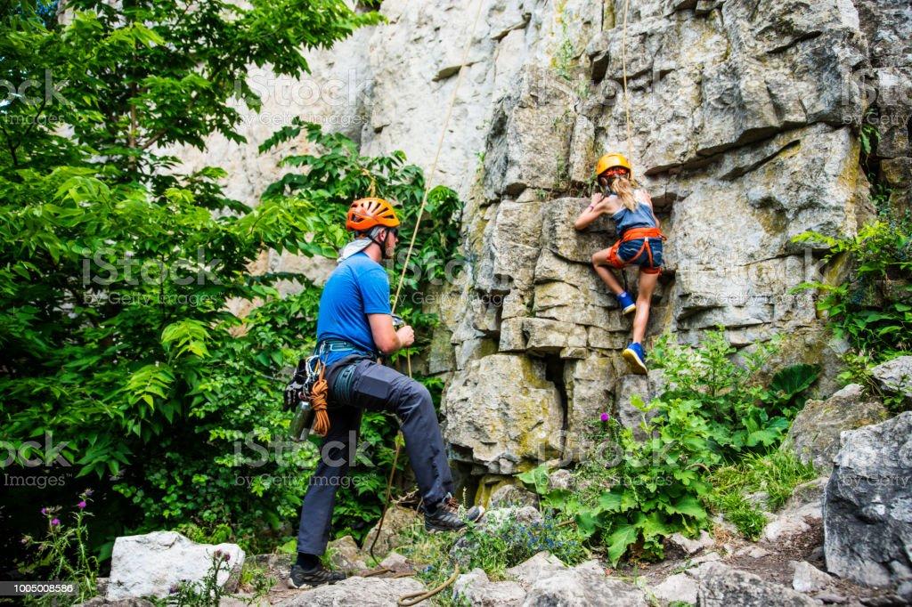 Une solide et athlétique jeune fille tandis que Regarde un instructeur d'escalade une paroi rocheuse avec le bon équipement d'escalade. - Photo