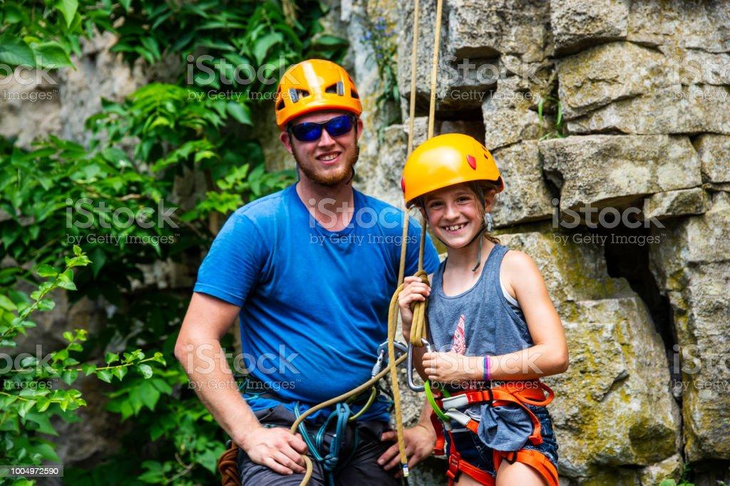 Une solide et athlétique jeune fille avec un instructeur escalade devant une paroi rocheuse. - Photo