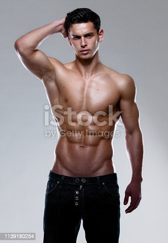 A shirtless, muscular, strong, athletic young man, posing in studio.