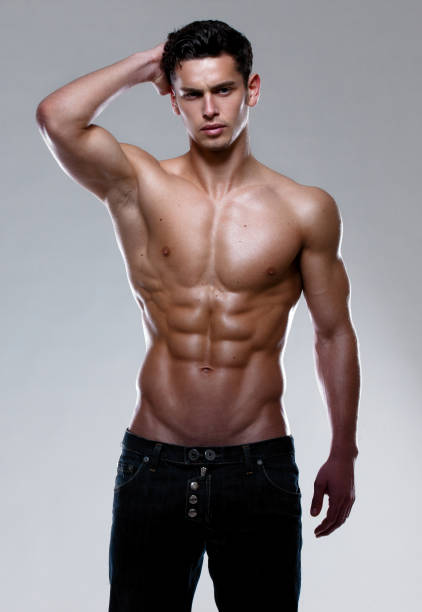 A strong athletic young man model showing six pack abs, holding his hand behind head. Vertical studio shot. A shirtless, muscular, strong, athletic young man, posing in studio. shirtless male models stock pictures, royalty-free photos & images