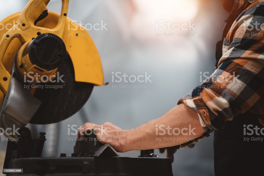 Strong bearded mechanic use angular grinding machine in metalworking plant. Work in service station. Servicing of machines and workflow at the factory stock photo