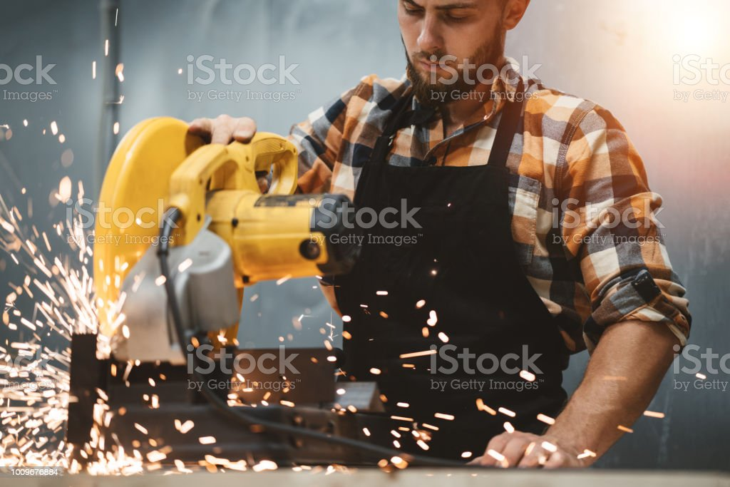 Strong bearded mechanic working on angular grinding machine in metalworking. Work in service station. Sparks fly apart. Flare effect stock photo