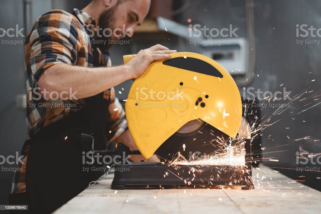 Strong bearded mechanic working on angular grinding machine in metalworking. Work in action. Sparks fly apart. Flare effect stock photo
