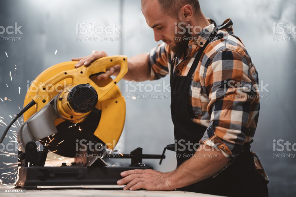 Strong bearded mechanic working on electrical angular grinding machine in metalworking factory. Work in service station. Sparks fly apart stock photo