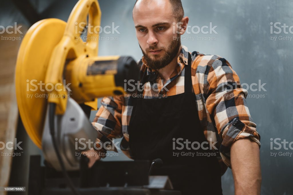 Strong bearded worker use angular grinding machine in metalworking. Work in service station stock photo