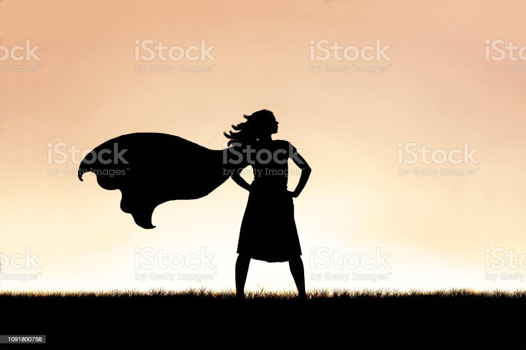 Strong Beautiful Caped Super Hero Woman Silhouette Isolated Against Sunset Sky Background stock photo