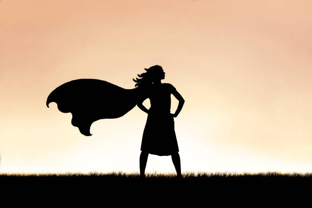 strong beautiful caped super hero woman silhouette isolated against sunset sky background - forza foto e immagini stock