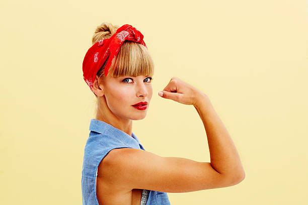 Strong blond woman flexing muscle stock photo