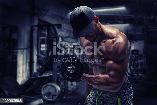 istock Strong bodybuilder man pumping up muscles after extreme workout . Bodybuilding concept background. 1050909886