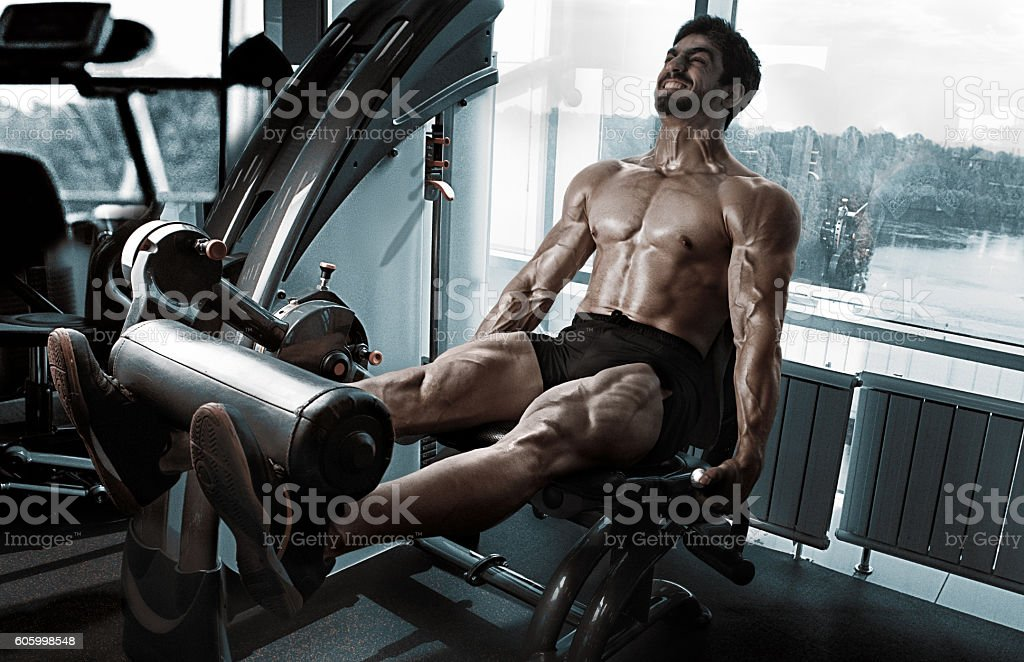 Strong bodybuilder training quads stock photo