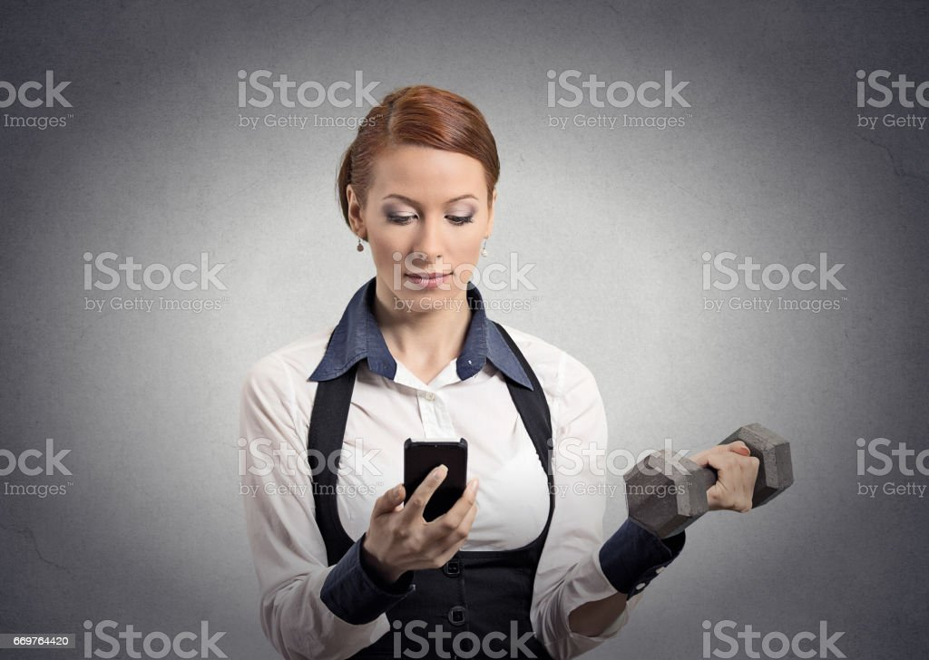 strong business woman reading news on smart phone, holding mobile, lifting weight stock photo