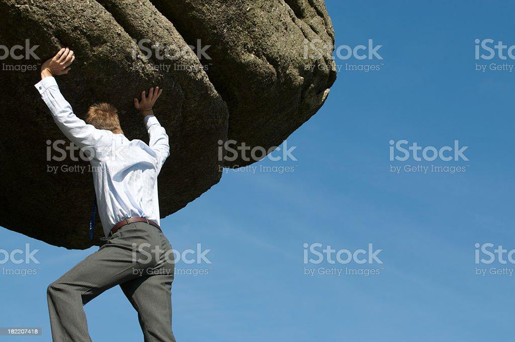Strong Businessman Heaving Massive Boulder into Sky stock photo