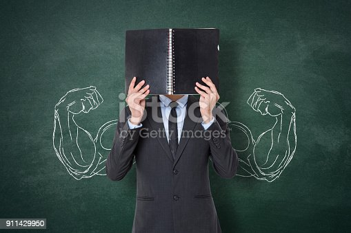 Strong businessman holding diary in front of his face with flexing muscles sketch on chalkboard