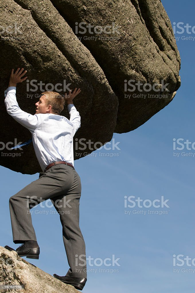 Strong Businessman Lifting Massive Boulder Outdoors in Blue Sky stock photo