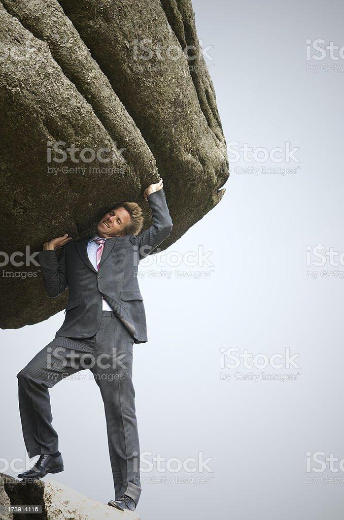 Strong Businessman Struggles to Lift a Big Boulder stock photo