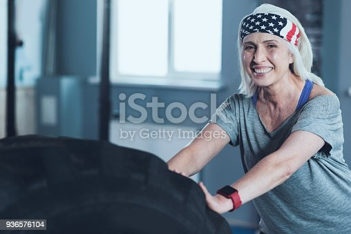 936573360 istock photo Strong cheerful senior lady training with heavy tire 936576104