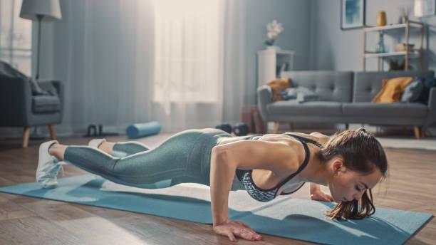 Starke selbstbewusste schöne Fitness-Mädchen in grau Athletische Sportbekleidung ist Push-Up-Workout-Übungen in ihrem hellen und geräumigen Apartment mit gemütlichen minimalistischen Interieur. – Foto