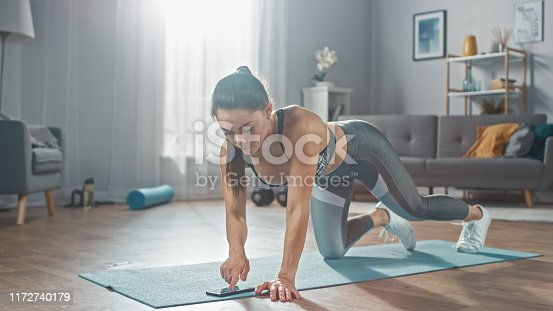 Strong Confident Fitness Girl in Grey Athletic Sportswear is Doing Push Up Workout Exercises While Using a Stopwatch on Her Phone. She is Training at Home in Her Bright Living Room with Cozy Interior.