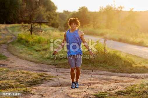 511849865istockphoto Strong confident sporty man jumping rope in park. Early summer morning training. 1028866438
