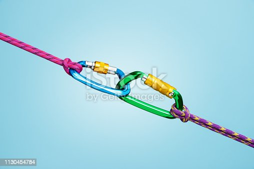 Strong connection with two locked carabiners and climbing rope on blue background