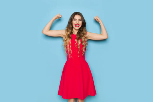 Strong Elegant Woman Is Flexing Biceps And Smiling Strong beautiful young woman in red dress is holding arms raised, smiling and flexing biceps. Three quarter length studio shot on blue background. dress stock pictures, royalty-free photos & images
