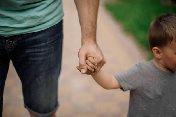 sterke vader hand met een kleine hand van zijn zoon - verduisterd gezicht stockfoto's en -beelden