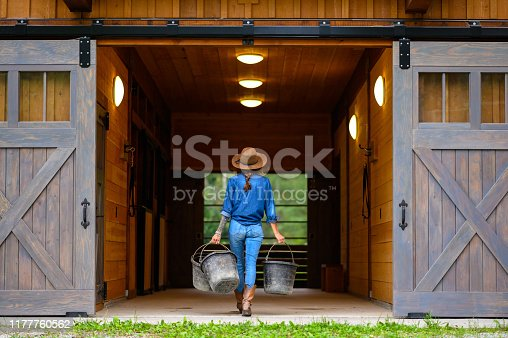 Female farmer working around her barn. Rancher working on a Canadian ranch. Empowered woman working in agriculture.