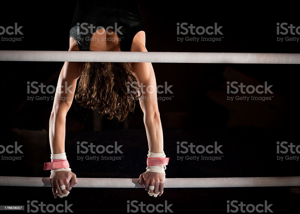 Strong Female Gymnast in Handstand atop Uneven Bars stock photo