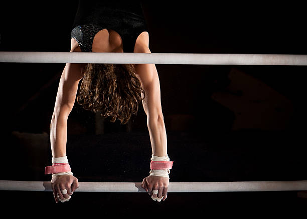 strong female gymnast in handstand atop uneven bars - uneven parallel bars stock photos and pictures