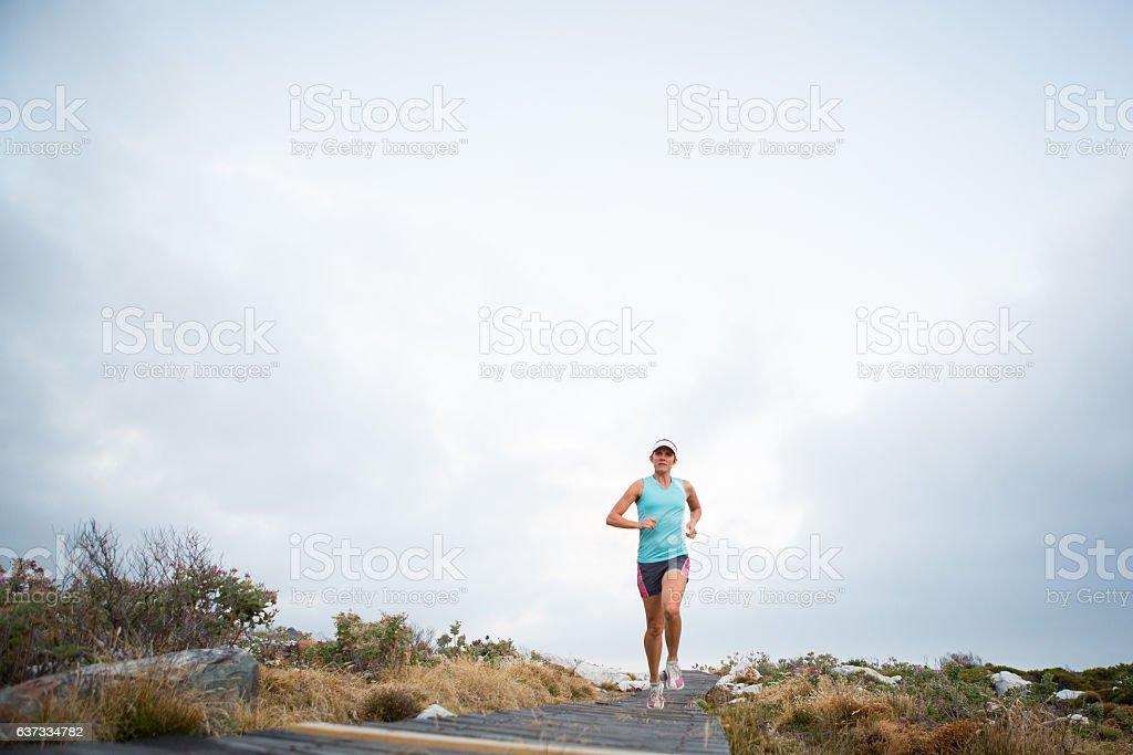 Strong female runs along a wooden path stock photo