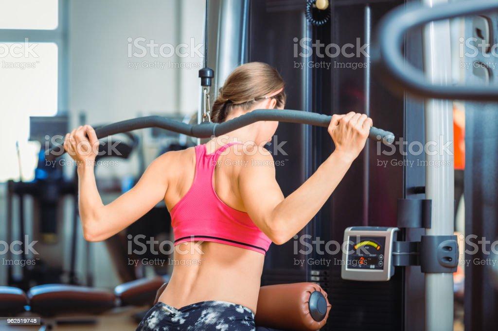 Forte ajuste mulher exercitando o pushdown lat para músculos das costas em um moderno centro de fitness - Foto de stock de Academia de ginástica royalty-free