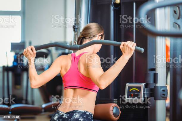 Foto de Forte Ajuste Mulher Exercitando O Pushdown Lat Para Músculos Das Costas Em Um Moderno Centro De Fitness e mais fotos de stock de Academia de ginástica