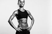 Young strong fitness woman posing in studio. Black and white image.