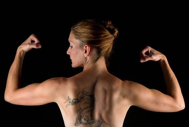 Strong forty something woman flexing stock photo