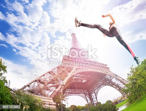 Dynamic shot from low angle of young talented sportswoman jumping near Eiffel Tower