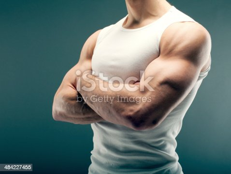 Male person with strong arms in white shirt over green background.